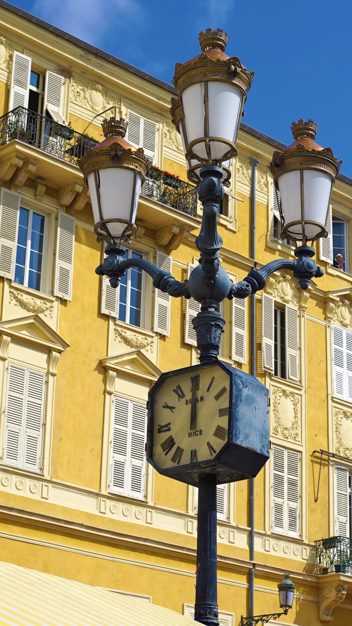 Clock in Nice against yellow brick